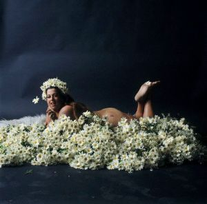 A paleskinned fat woman with dark hair lies front-down and naked upon a bed of white daisy-like flowers. Her head is held high with a wide smile looking into the camera. We can see her head, one shoulder, a bit of buttock, and her feet up in the air. One hand is just visible holding a flower next to her face, and we see another flower held between her toes so it lies just on the sole of one foot.