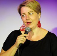 Middle aged white woman speaking into hand-held microphone.
