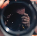 Photograph taken of the photographers reflection in a mirror, mostly what we see is the camera with some fingers and some forehead