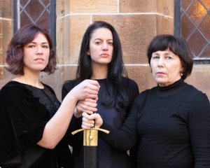 Three brunette women of varying ages grasping a sword hilt.