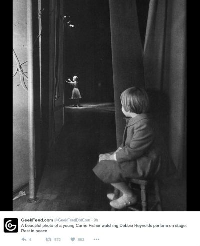 B&W photo of a toddler girl on a stool watching a woman on stage in the distance.
