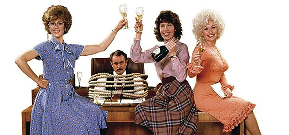 Three woman sit on a large business desk, toasting each other with champagne. Seated behind them is their male boss, tied to his office chair.