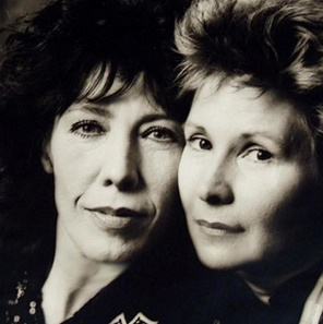 A close-up portrait of two middle-aged pale-skinned women, their faces close and touching