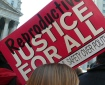 Photo of banner at a rally, banner reads REPRODUCTIVE JUSTICE FOR ALL